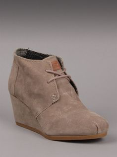 TOMS® Shoes Taupe Suede Women's Desert Wedges.  The fine art of shoe making is evident with TOMS shoes fashion. The Desert Wedge in taupe suede has a soft suede uppper with matching laces for a monochromatic look. A leather TOMS patch on the tongue and the TOMS classic blue patch on the heel make these distinctive TOMS shoes.