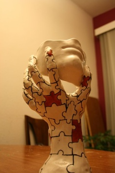clay sculpture I made in highschool. free form hand and a clay mask of my face.