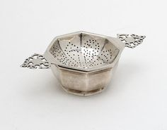 An antique silver tea strainer. London, 1935. From Goldsmith & Perris at Alfies