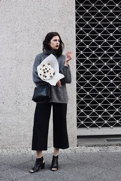 Elisa from the Fashion- and Lifestyleblog www.schwarzersamt.com is wearing black culottes from TOPSHOP, black mules from GOERTZ, a cozy turleneck sweater from COS and a celine trio lookalike bag from C&A. Carrying flowers from bloombox by blossom. It's a perfect spring / autumn look with a grey cozy wool sweater