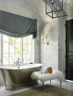 The bathroom features so many beautiful, classic pieces like the soaking tub, carrera marble for days, a fabulous oversized lantern and stylish sconce along with a fun Mongolian lambswool bench. I love black interior doors.....