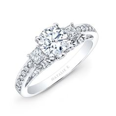 NK25815<br /> A magnificant piece, this 18k white gold Natalie K diamond engagement ring glimmers with a unique design showcasing pave and bezel set brilliant round diamonds and two prong set princess cut side stones.