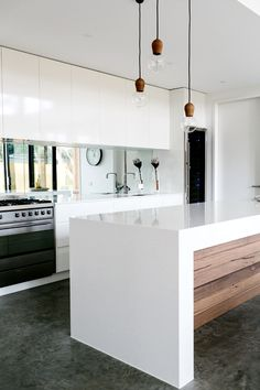 very pretty faucet and light fixtures. lovely color for the concrete floor. very clever light bouncing with the mirrored backsplash and floor length windows adjacent. lacquered countertop and cabinets are too sheeny, though; matte-ish white granite would look crisper | barwon heads, victoria