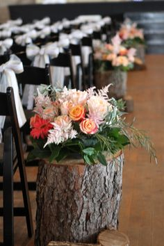 the wedding ceremony is decorated with white bows on the chairs and tree stumps topped with flowers lining the wedding aisle - thereddirtbride.com - see more of this wedding here
