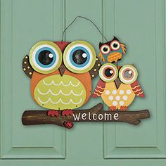 """NEW! Owls Metal Welcome Sign - This vibrant owl trio will greet visitors with a whimsical welcome! Perfect for your front door, porch or patio, this metal and wood sign brings the fun to your home, trailer or cottage. Hangs with included metal wire. (14""""L x 3/4""""W x 12-1/2""""H) $14.98 CAD"""