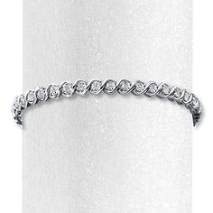 Ribbons of sterling silver embrace round diamonds along this stylish bracelet for her. The 7.5-inch bracelet has a total diamond weight of 1/20 carat and secures with a tongue clasp. Diamond Total Carat Weight may range from .04 - .06 carats.