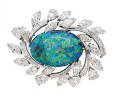 A Black Opal and Diamond Brooch  Centering an oval black opal measuring  amid trailing baguette-cut, marquise-cut and pear-shaped diamond leaves.