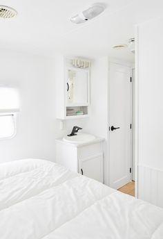 Tiny Home Living, sink in bedroom room, storage ideas, white walls Modern Tiny House, Tiny House Design, Motorhome, Caravan Vintage, Vintage Airstream, Travel Trailer Remodel, Travel Trailers, Trailer Decor, Camper Makeover