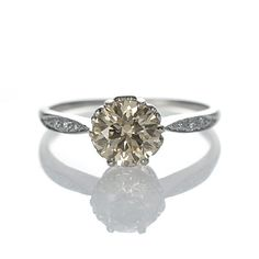 Leigh Jay Nacht Inc. A Round Brilliant Cut diamond with a champagne hue set low in a platinum ring with a six prong crown center and slender shoulder with detailed design with millegrained edges. This ring is an exact replica of an Edwardian original.