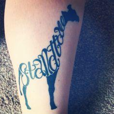 Giraffe tattoo with 'Stand Tall' intertwined.