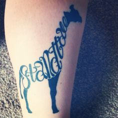 Giraffe tattoo with 'Stand Tall' intertwined.