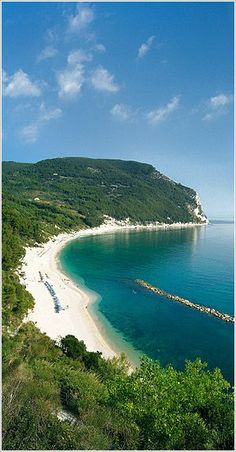 The San Michele beach in Sirolo, Italy ....is a long, white, sandy beach sheltered by green cliffs. It is mostly public beach and only some sections have a beach service with sun loungers and umbrellas