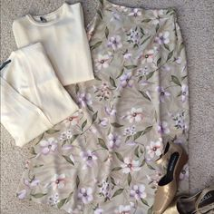 """Floral Tea Length Skirt A pretty  beige, ivory and pastel floral print for Spring and Summer. Pairs well with the ivory sweater set and ankle strap wedged in my closet as pictured. Bundle discounts Also nice with white, lavender, sage or soft coral. The 100% Polyester fabric is lightweight and drapes nicely. Machine wash. Hidden back zipper. Elastic waistband insets on the back are shown in the 3rd photo. Waist 14 - 17"""", lying flat. Length  33"""". Hip 21"""", lying flat. Excellent condition…"""