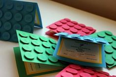 Make invitations using colored card stock, a one inch hole punch, and 3D foam tape. | How To Throw The Ultimate LEGO Birthday Party