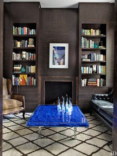 In the library, a Richard Prince photograph overlooks a display of vintage Murano-glass decorative objects on an Yves Klein cocktail table. The paneling is palm wood accented with bronze.