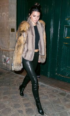 Kendall Jenner wears a fur coat, crop top, leather pants, and lace-up boots