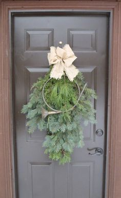 Seasonal swag with burlap bow and brass hunting horn. Trimmed with evergreen spruce and juniper. Suspended with magnetic knob on shed door