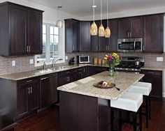 This contemporary kitchen design features Hard Maple cabinets in Espresso with Classic Raised Panel style #10. The countertops are Granite certified by Kitchen Magic in New Venecian Gold.