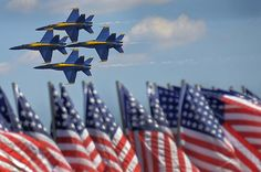 The Blue Angels - Boeing F/A-18 Super Hornet planes - fly in formation past a line of U.S. flags