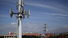 Two neighboring cell towers overlap to provide thorough coverage for mobile device users in the area. Towers typically have a range extending miles outward.