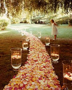 Large hurricane vases containing floating candles are placed like so many beacons on either side of a path strewn with rose petals in shades of pink and yellow. If you're picking from your own garden, pluck them early in the morning, when roses are their freshest.
