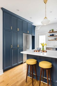 Blue floor to ceiling kitchen cabinets accented with brass pulls frame a stainless steel refrigerator and are fixed facing a blue peninsula seating yellow backless barstools at a white quartz countertop lit by white glass schoolhouse pendants.