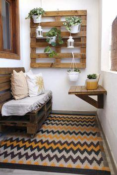 petit espace extérieur, balcon fleuri, déco jardin récup, tapis motifs graphiques en orange, ivoire et noir, meuble en palettes en marron foncé, mur végétal en bois de palette avec des pots blancs, petite table pliable en palettes