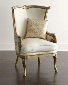 Handcrafted chair. Carved frame made of mahogany with a brushed golden finish. Leather seat cushion; polyester/rayon upholstery on inside back and inside arms; polyester/linen upholstery on outside ba