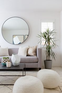 Round mirror, grey linen sofa, rope coil ottomans, plant, modern geometric living room design - neutral but interesting