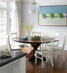 Green Apple Dining Area with blue-gray walls, circles curtains, dark round wood table and white x-back chairs - Greenwich Home by Muse Interiors