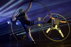 While masterfully controlling his balance, an acrobat rotates on the floor in a Cyr Wheel ring that becomes an extension of his body. The act is full of dyn Circus Art, Floor, Pure Products, Ring, Rings, Boden, Flooring, Quarter Ring, Jewelry Rings