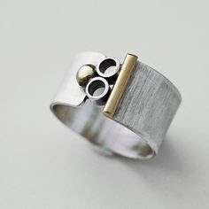 Mixed metal, sterling silver, wide band Mod ring with 14K gold filled accents. This handmade, modern ring is a wonderful addition to your collection. I added the silver tubes and gold filled accents and oxidized it to bring out the details. Brush matte finish. Width: 1/2 inch Size: 8.5 For more handmade rings: https://www.etsy.com/shop/cyndiesmithdesigns?section_id=5186906