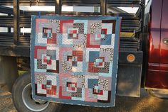 I really like the geometric squares within squares and how my eye darts all over the whole quilt.  I also like the earthy reds, denim blues and muted greys.