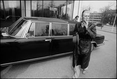 David Bowie smokes a cigarette next to his limousine in 1976