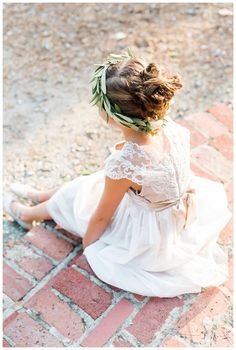 Flower girl with a crown of olive leaves. Image by Rustic White Photography.