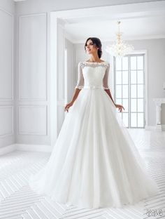 Sans Pareil Bridal Collection: 884 - Lace appliques on illusion yoke with lace-trimmed three-fourth sleeves and A-line skirt