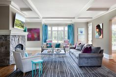 This vibrant family room features a beautiful gray hue seen in the soft wall color, suede sofa and patterned area rug. Pops of bright aqua and deep purple in the satin curtains, throw pillows, wall art and end table add a fun vibe to the space.