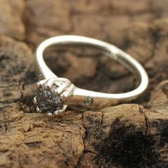 Silver engagement ring with rough diamond and twin set pave diamonds on either side of the main gem