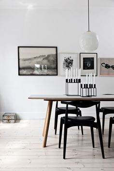 Very white walls. Black framed art & photos. Black chairs. Wood table. White painted floorboards.