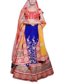 Saroj Jalan creates a marvellous outfit with traditional colours like red, blue and yellow and brings to you this lehenga that is perfect for a bride. The velvet lehenga features a pretty golden thread work and contrasting orange, red and blue borders patched and festooned with golden thread work. It has been teamed with a red velvet fully embroidered princess panel blouse with borders at the sleeves. A yellow net dupatta with buti work and contrasting borders comes as a part of the set. A…