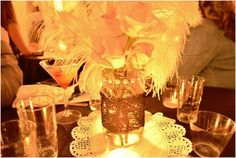 mason jar with lace, pearls and feathers centerpiece. very 20s
