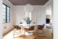 A bright dining space with modern leather chairs and a pendant light fixture with a wallpapered ceiling