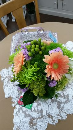 Coral/ peach gerbera daisy, green spider mums, trick dianthus, mini green hydrangea, green hypericum, and lavender stock