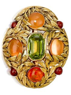 Louis Comfort Tiffany for Tiffany & Co. attrb. - An Arts and Crafts peridot, fire opal and carnelian brooch, circa 1915. Of oval form with gold foliate field, centred by a modified rectangular-cut peridot, weighing approximately 3.65 carats, enhanced with fire opal cabochons and carnelian beads; signed Tiffany & Co., numbered; mounted in 18k gold; length: 1 1/2in. #LouisComfortTiffany #ArtsAndCrafts #brooch