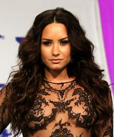 Demi Lovato Long Wavy Hairstyle. Demi Lovato looks lovely here in a sexy, striking, wavy hairstyle. Having an oblong face shape and high, rounded hairline, Demi's face looks best in 'dos with a grown out fringe and longer layers around the face. This voluminous layered cut creates a nice frame around her cheekbones and allows her hair's natural texture to do its thing, adding body and bounce all over.