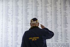 A USS Arizona survivor salutes the remembrance wall of the USS Arizona during a memorial service for... - Provided by AFP
