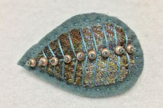 A stylish felt and tweed brooch decorated with beads
