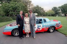 President Ronald Reagan posing with race car driver Richard Petty and his wife Lynda in front of Petty's car at the White House. 6/27/85.