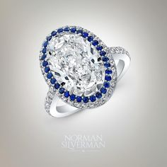 The ancients believed an enormous sapphire cradled the world, its reflection painting the sky blue. Here, the deepest of blue sapphires surround a diamond of incredible beauty. | Oval cut diamond surrounded with blue sapphire set in platinum pavé ring.
