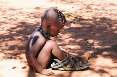 Photography Competition 2016 | National Geographic Traveller (UK) A young Himba girl plays with her father's shoe, made from car tyres. Namibia. February 2014